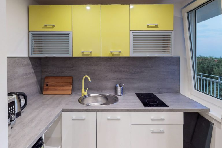 żółte szafki w kuchni w mieszkaniu na wynajem